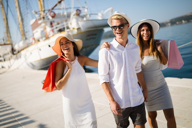 Concetto di vacanza, viaggio, mare, amicizia e persone. amici sorridenti che si divertono insieme