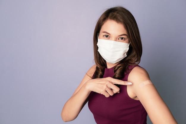 Donna asiatica vaccinata che indossa il dito puntato della maschera protettiva per il viso che mostra una benda di gesso sul braccio dopo un'iniezione di vaccino contro il coronavirus, la vaccinazione contro il covid-19 e il concetto di immunizzazione antivirale.