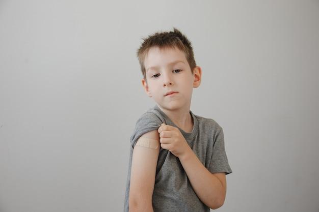 Ragazzo vaccinato che mostra il braccio dopo l'iniezione del vaccino covid-19 covid