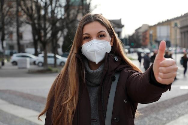 Campagna di vaccinazione. ottimista giovane donna che indossa la maschera protettiva ffp2 kn95 che mostra i pollici in su in abiti invernali all'aperto.