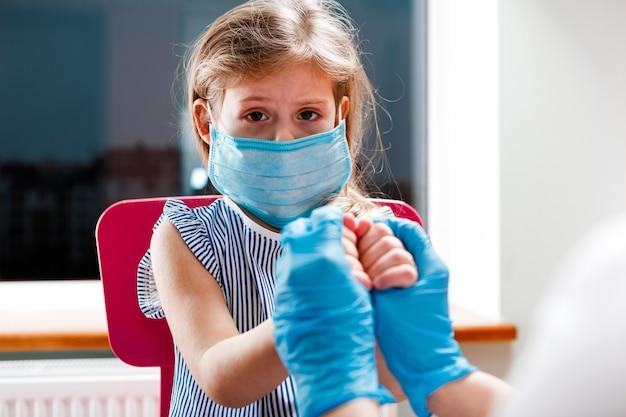 Vaccinazione dei bambini. medico che esamina un bambino in un ospedale. covid-19