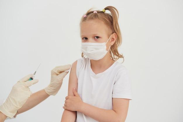 Concetto di vaccinazione. la mano del medico vaccina una bambina carina con una maschera protettiva su uno sfondo bianco, primo piano.