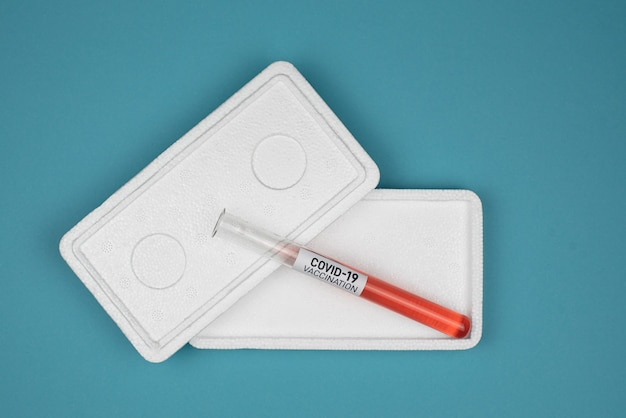 Il vaccino contro il caronavirus covid-19 si trova in una cassetta di sicurezza su un tavolo blu. concetto medico e sanitario