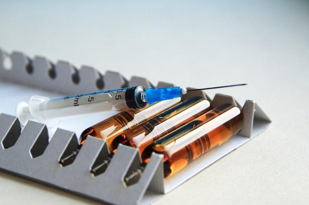 Fiale di vaccino e una siringa monouso su sfondo chiaro