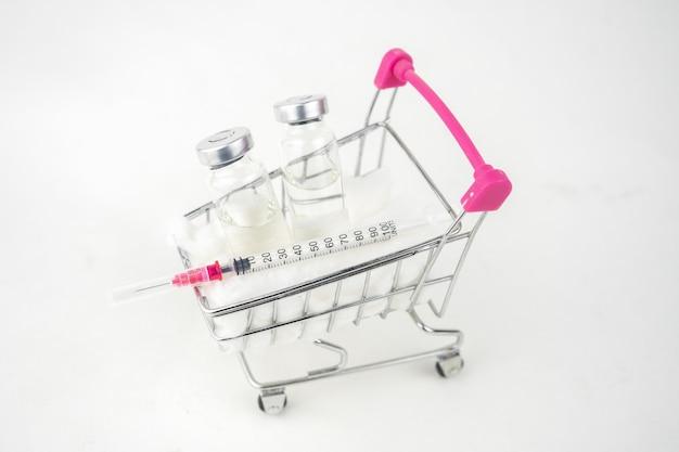 Bottiglia e siringa del vaccino in un carrello. concetto di trattamento del vaccino. isolato