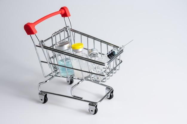 Bottiglia e siringa di vaccino in carrello o carrello su fondo bianco Foto Premium