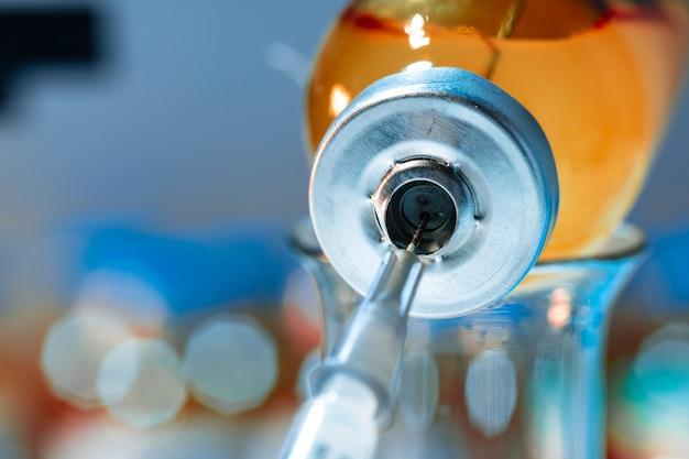 Bottiglia di vaccino con una siringa che prende il vaccino da vicino