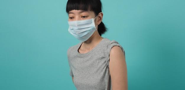 Concetto di vaccino. donna in attesa dell'iniezione del vaccino contro il coronavirus da parte del medico. donna asiatica con la spalla aperta della mascherina medica e la parte superiore del braccio su priorità bassa verde blu. aspettando la vaccinazione.