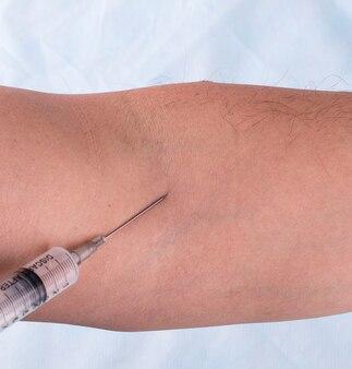 L'iniezione di vaccino in mano all'uomo