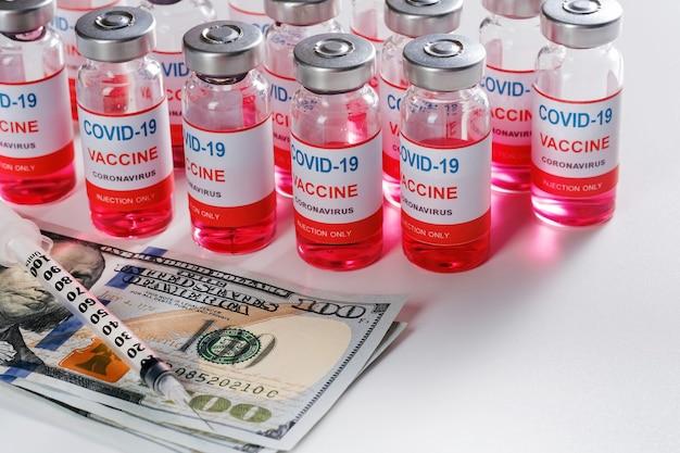 Fiale di vaccino, siringhe e denaro per l'acquisto o lo scambio di vaccino.