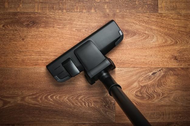 Spazzola dell'aspirapolvere sul pavimento di legno