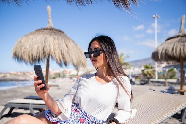 Ragazza vanitosa usa il suo smartphone in spiaggia in vacanza in una località turistica tropicale.