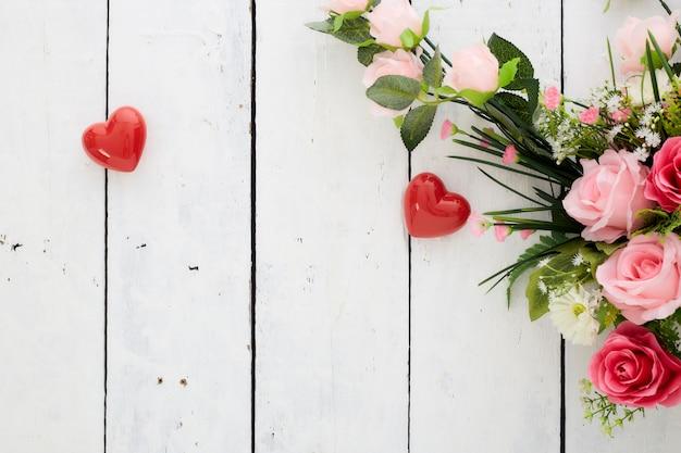 San valentino romantico cuore rosso e bouquet di fiori colorati sulla tavola di legno bianca