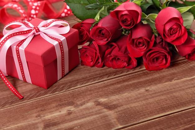 Fondo del biglietto di s. valentino del contenitore di regalo e delle rose rosse su legno. spazio per la copia