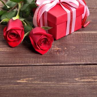 Fondo del biglietto di s. valentino del contenitore di regalo e rose rosse su legno