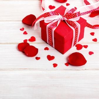 Priorità bassa del biglietto di s. valentino del contenitore di regalo e dei petali di rosa su legno bianco
