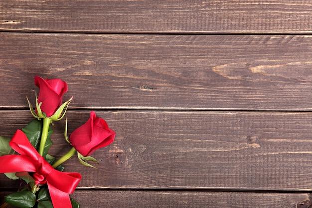 Priorità bassa del biglietto di s. valentino delle rose rosse su legno. spazio per la copia