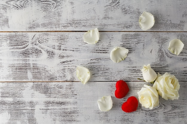 Il fondo del biglietto di s. valentino, i fiori della rosa di bianco ed i petali hanno sparso su legno rustico bianco, vista superiore con lo spazio della copia. mockup di amanti felici giorno