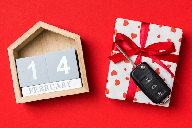 Calendario di san valentino e confezione regalo con nastro rosso e auto chiave. lay piatto