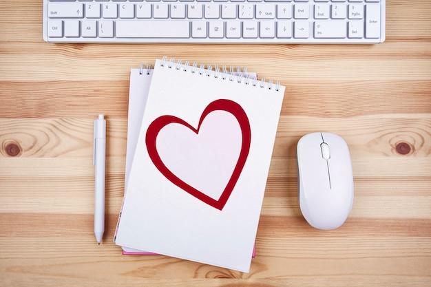 Cartolina di san valentino sul desktop dell'ufficio. concetto festivo, romantica dichiarazione d'amore. vista dall'alto, copia dello spazio.