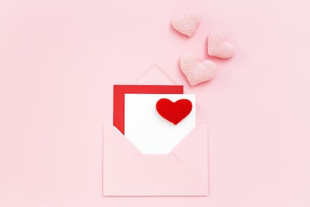 Cartolina di san valentino in busta rosa con cuori rossi e rosa. copia spazio, piatto laici.