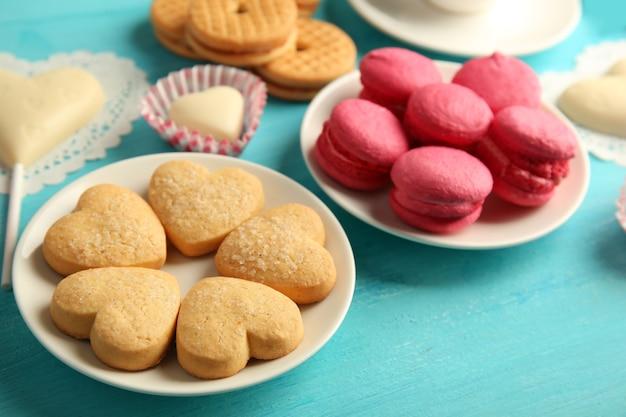 Concetto di san valentino. composizione di biscotti e caramelle su sfondo blu