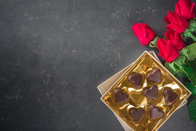 Sfondo di san valentino con cuori di cioccolato e rose rosse