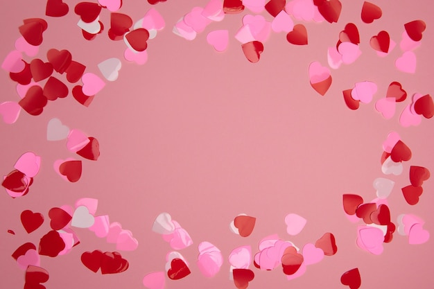 Composizione di san valentino con copia spazio. cornice fatta di coriandoli cuori rossi e rosa su sfondo pastello. primo piano, vista dall'alto, copia dello spazio