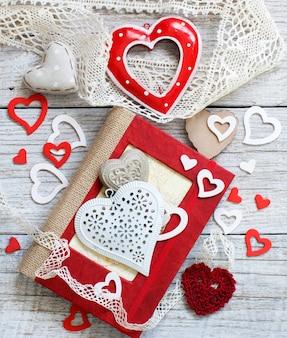 Composizione di san valentino con cuore e taccuino su un tavolo di legno