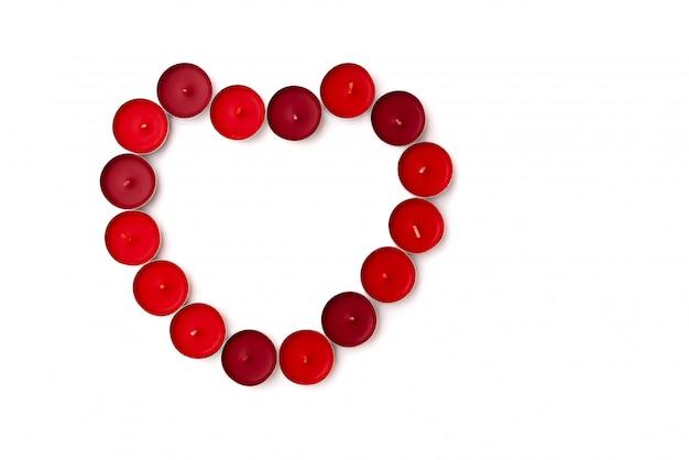 Concetto di san valentino, sfondo bianco con cuori rossi e candele
