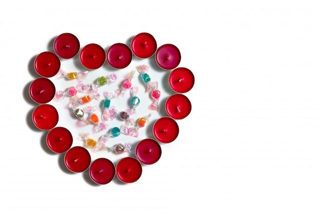 Concetto di san valentino, sfondo bianco con cuori rossi e caramelle dolci