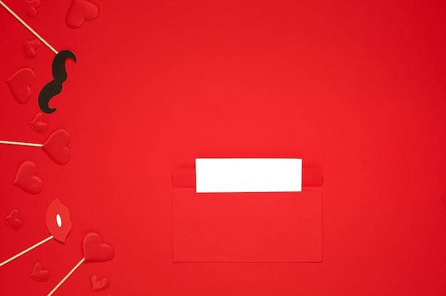 San valentino. busta, biglietto vuoto per il testo, baffi, labbra rosse e cuore su sfondo rosso