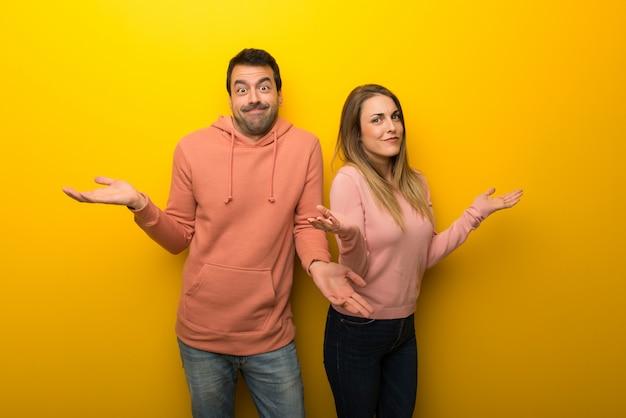 Nel giorno di san valentino gruppo di due persone su sfondo giallo con dubbi sollevando mani e spalle