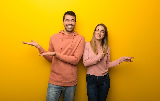 Nel giorno di san valentino gruppo di due persone su sfondo giallo con copyspace immaginario sul palmo della mano per inserire un annuncio