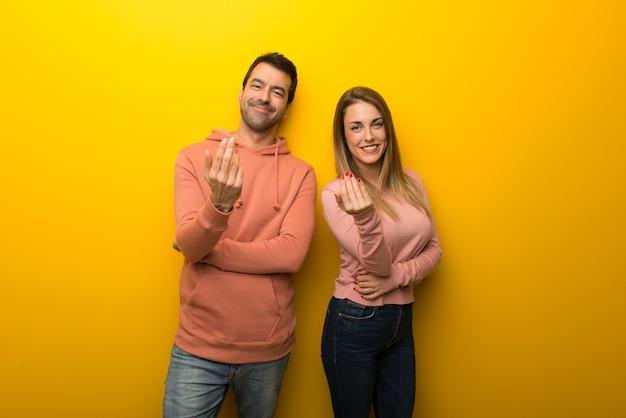 Nel giorno di san valentino gruppo di due persone su sfondo giallo che invita a venire con la mano. felice che tu sia venuto