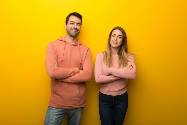 Nel giorno di san valentino gruppo di due persone su sfondo giallo mantenendo le braccia incrociate in posizione frontale