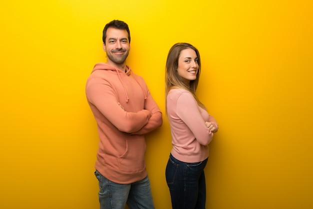 Nel giorno di san valentino gruppo di due persone su sfondo giallo mantenendo le braccia incrociate in posizione laterale mentre sorridendo