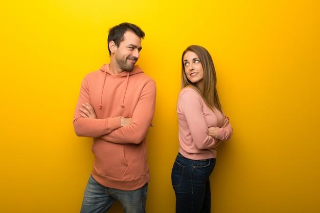 Nel giorno di san valentino gruppo di due persone su sfondo giallo guardando oltre la spalla con un sorriso
