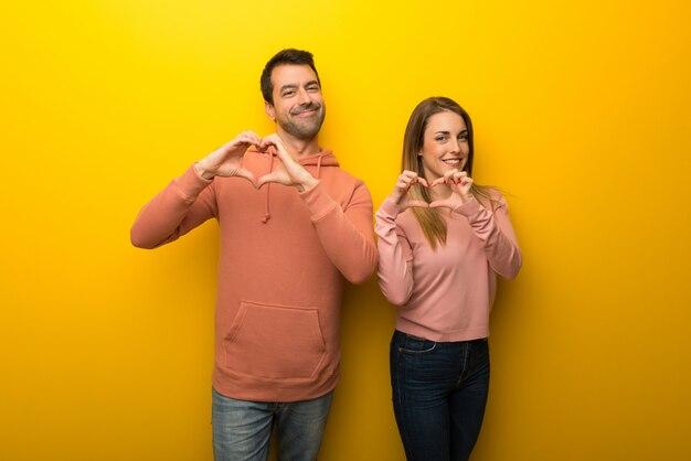 Nel giorno di san valentino gruppo di due persone su sfondo giallo, rendendo il simbolo del cuore a mano