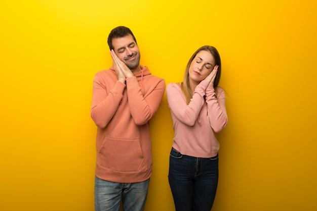 Nel giorno di san valentino gruppo di due persone su sfondo giallo che fa gesto di sonno in espressione dorable