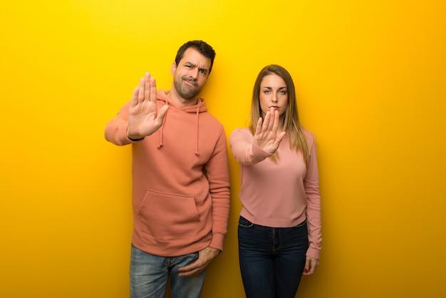 Nel giorno di san valentino gruppo di due persone su sfondo giallo che ferma il gesto negando una situazione che pensa in modo sbagliato Foto Premium