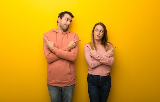 Nel giorno di san valentino gruppo di due persone su sfondo giallo che punta ai laterali avendo dubbi