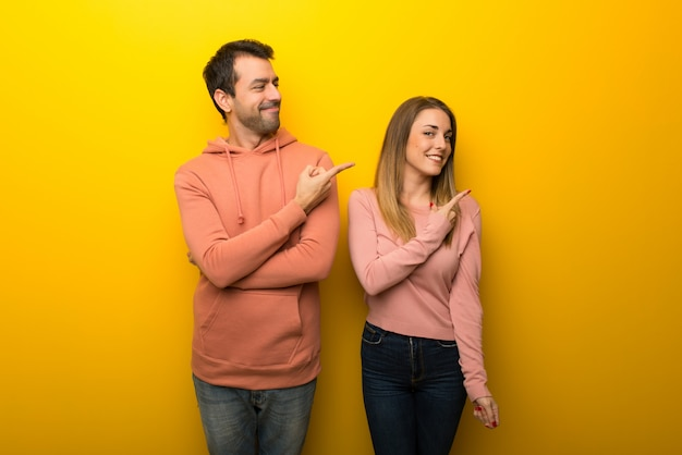 Nel giorno di san valentino gruppo di due persone su sfondo giallo che punta al lato per presentare un prodotto