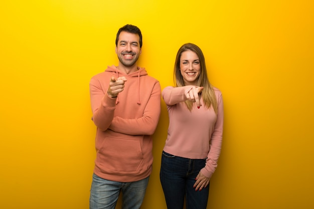 Nel giorno di san valentino un gruppo di due persone su sfondo giallo punta il dito verso di te con un'espressione fiduciosa
