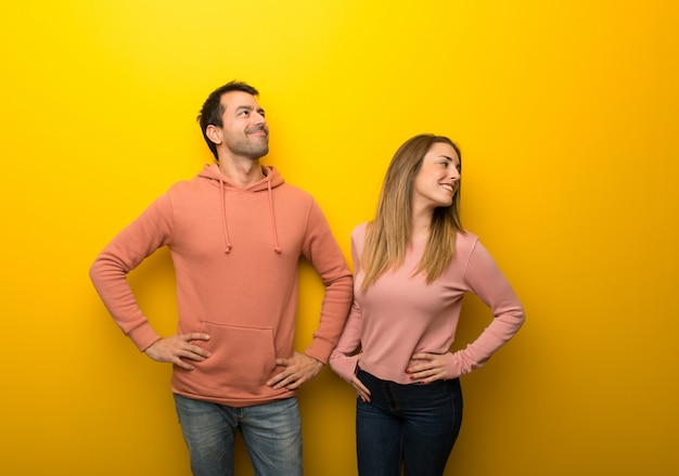 Nel giorno di san valentino gruppo di due persone su sfondo giallo in posa con le braccia in anca e ridendo