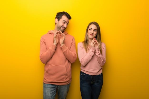 Nel giorno di san valentino gruppo di due persone su sfondo giallo che intrigano qualcosa