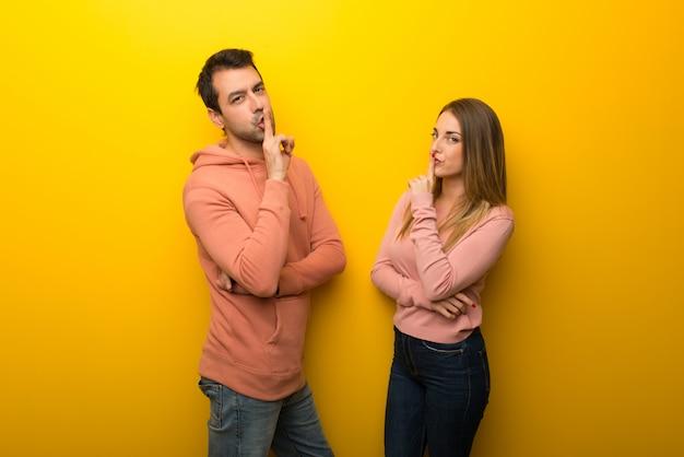 Nel giorno di san valentino gruppo di due persone su sfondo giallo che mostra un segno di chiusura della bocca e il gesto del silenzio