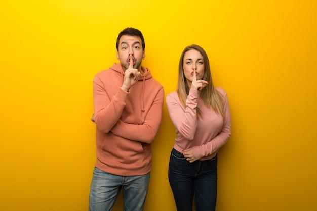 Nel giorno di san valentino gruppo di due persone su sfondo giallo che mostra un segno di silenzio gesto mettendo il dito in bocca