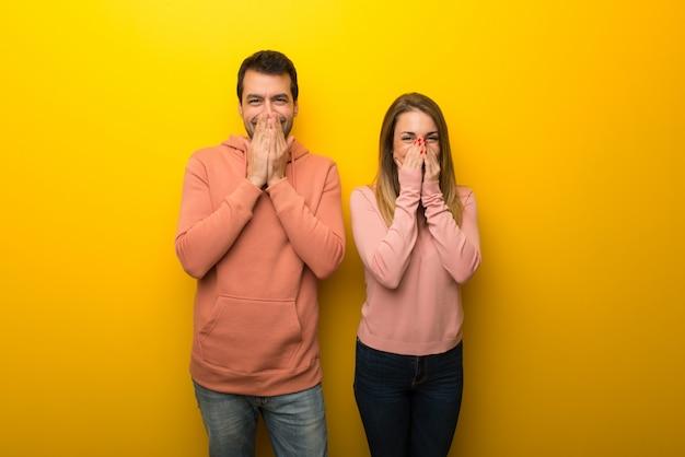 Nel giorno di san valentino gruppo di due persone su sfondo giallo sorridente molto mentre copre la bocca