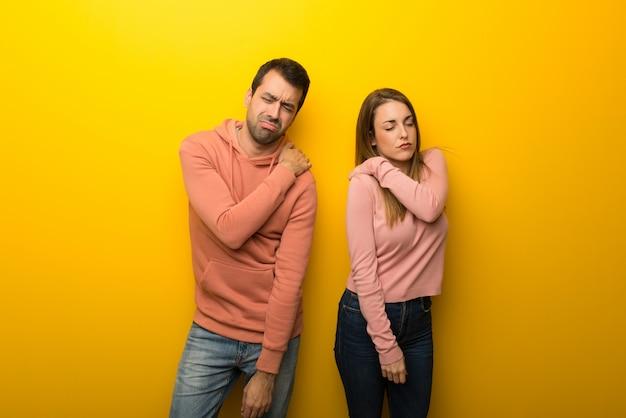 Nel giorno di san valentino gruppo di due persone su sfondo giallo che soffrono di dolore alla spalla per aver fatto uno sforzo